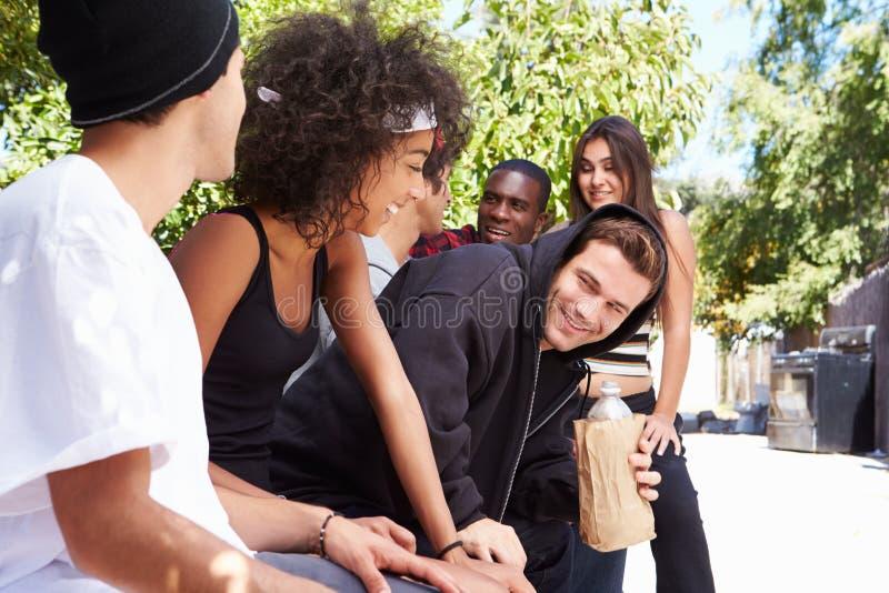 Gruppo dei giovani in alcool bevente dell'ambiente urbano immagini stock libere da diritti