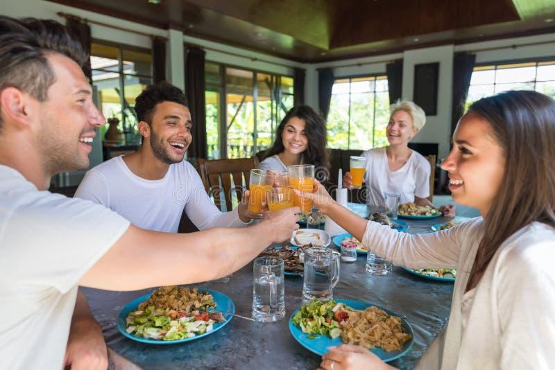 Gruppo dei giovani che mangia prima colazione insieme, bevanda interna dell'alimento di mattina della cucina degli amici fotografia stock