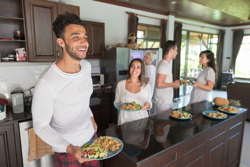 Gruppo dei giovani che mangia prima colazione insieme, bevanda interna dell'alimento di mattina della cucina degli amici fotografie stock libere da diritti