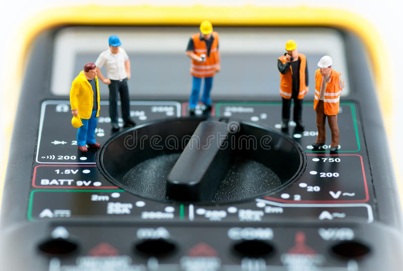 Gruppo dei lavoratori miniatura sopra il multimetro Macro foto fotografie stock