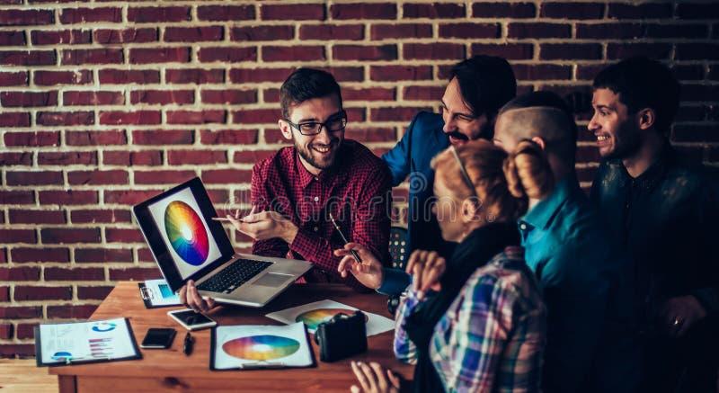 Gruppo dei progettisti nel posto di lavoro davanti ad un Di aperto del computer portatile fotografia stock libera da diritti