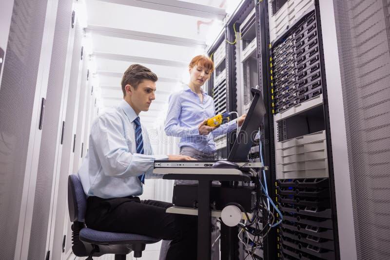 Gruppo dei tecnici che usando l'analizzatore digitale del cavo sui server immagine stock