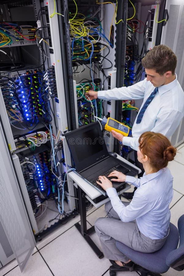Gruppo dei tecnici che usando l'analizzatore digitale del cavo sui server immagine stock libera da diritti