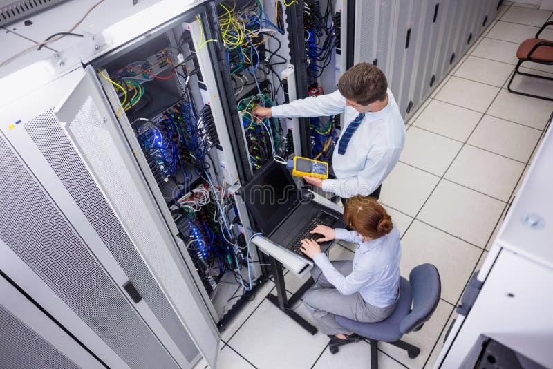 Gruppo dei tecnici che usando l'analizzatore digitale del cavo sui server fotografia stock libera da diritti