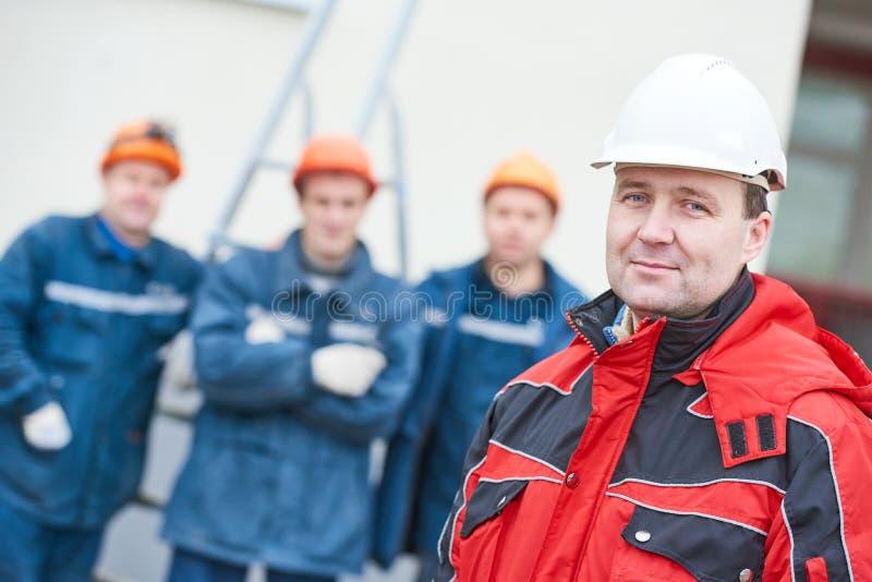 Gruppo dei tecnici dei muratori con il caporeparto nella parte anteriore immagini stock