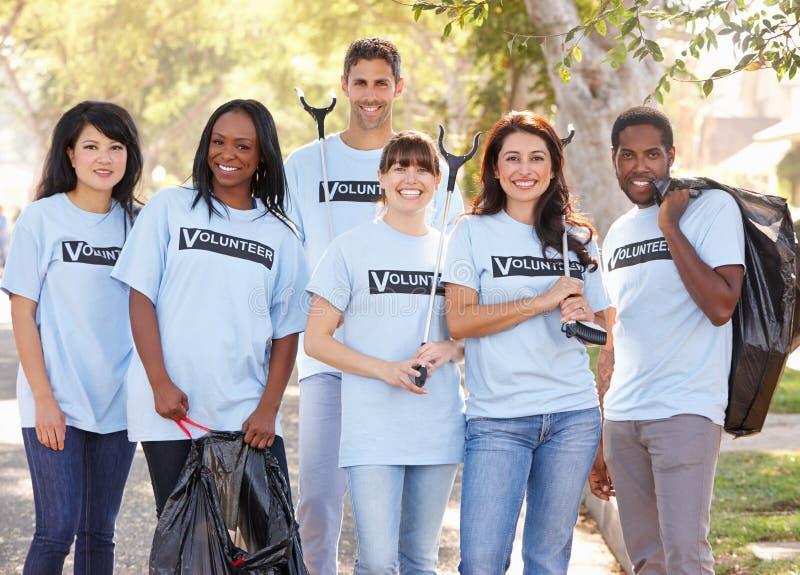 Gruppo dei volontari che prendono lettiera in via suburbana fotografie stock libere da diritti