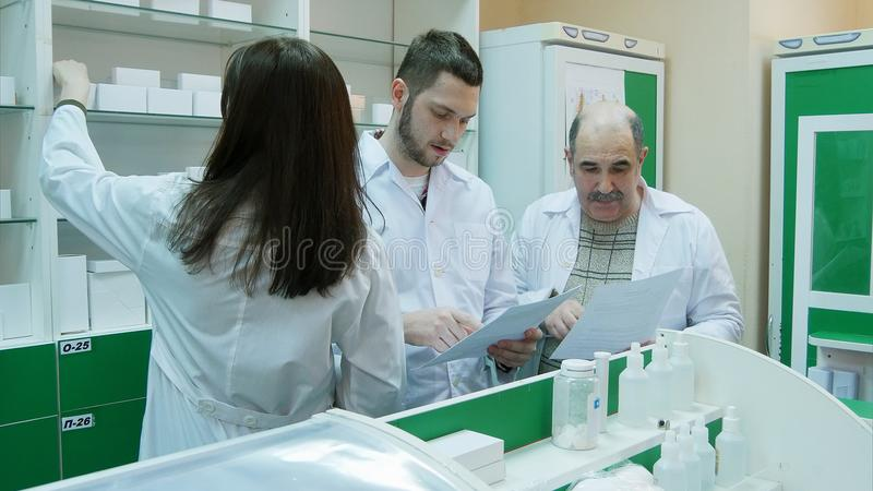 Gruppo del farmacista che controlla i documenti e medicina alla farmacia fotografia stock libera da diritti