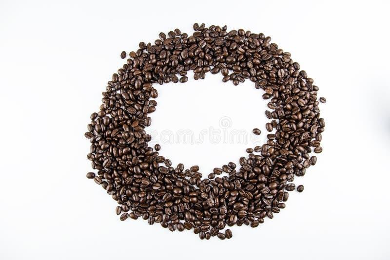 Gruppo del primo piano di chicchi di caffè arrostiti su fondo bianco Reticolo del cerchio fotografia stock