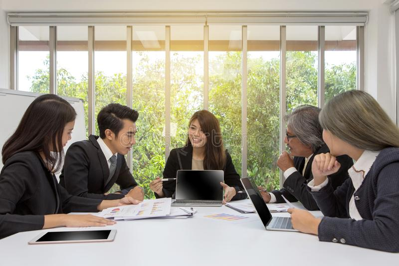 Gruppo dell'affare asiatico che posa nella sala riunioni 'brainstorming' di lavoro sulla tavola in una stanza Gente asiatica Uomi fotografie stock libere da diritti