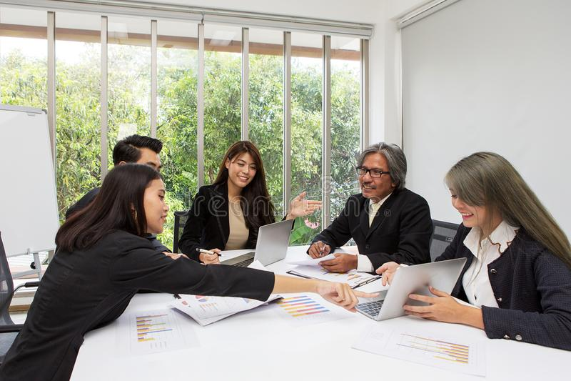 Gruppo dell'affare asiatico che posa nella sala riunioni Reggiseno di lavoro del gruppo fotografie stock