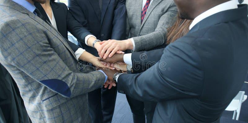 Gruppo dell'uomo d'affari in mani commoventi del vestito insieme Fuoco selettivo immagini stock