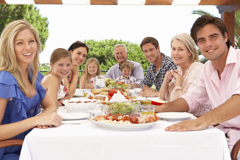 Gruppo della famiglia allargata che gode insieme del pasto all'aperto fotografie stock