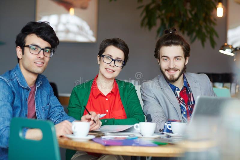 Gruppo della gente di affari creativa che si incontra in caffè fotografia stock