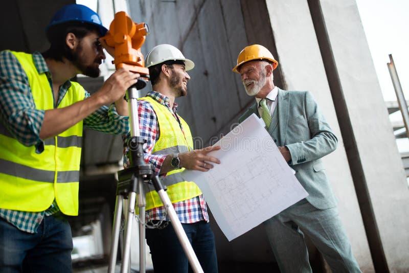 Gruppo della gente di affari nel gruppo, in architetto ed in ingegnere sui documenti del controllo del cantiere fotografia stock
