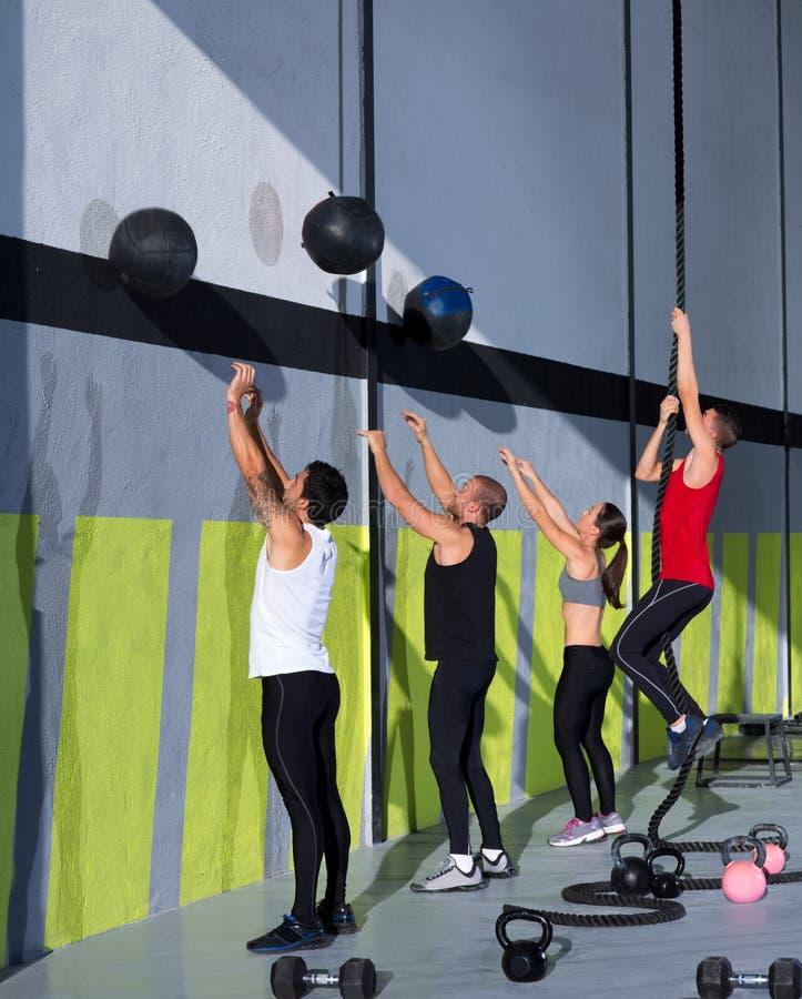 Gruppo della gente di allenamento di Crossfit con le palle e la corda della parete immagine stock libera da diritti