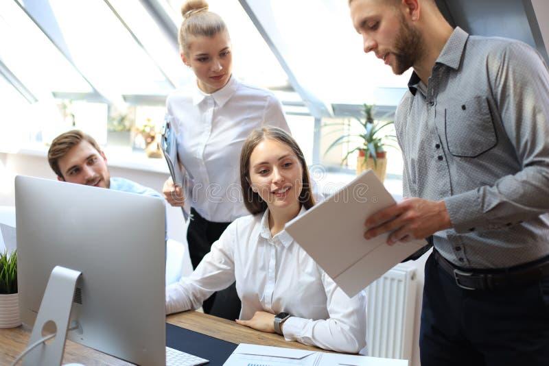 Gruppo della giovane impresa sulla riunione nel 'brainstorming' interno dell'ufficio luminoso moderno, lavorando alla compressa e immagini stock