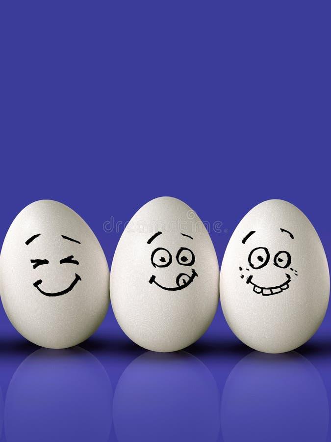 Gruppo delle uova di Pasqua, con i fronti divertenti, su fondo variopinto fotografia stock