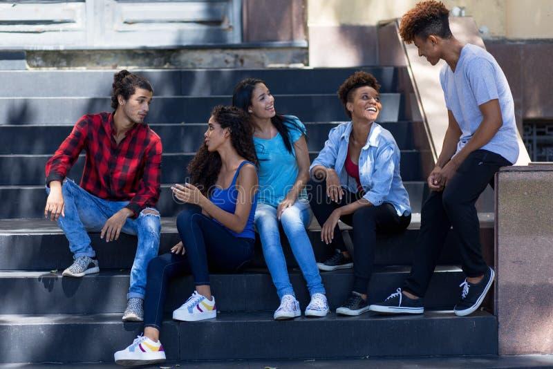 Gruppo di abitante dell'America latina di conversazione e di giovani immigrati adulti ispanici in città fotografie stock