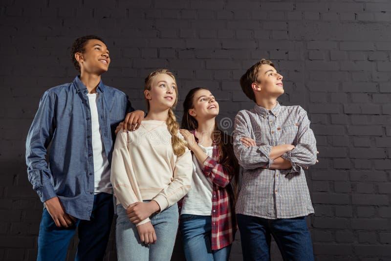 gruppo di adolescenti alla moda che stanno insieme davanti al muro di mattoni nero fotografie stock