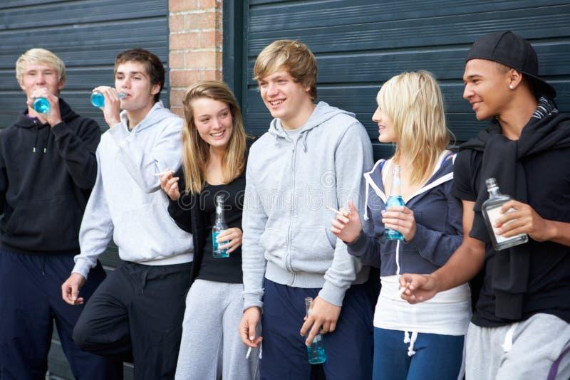 Gruppo di adolescenti che appendono insieme fuori all'esterno fotografie stock