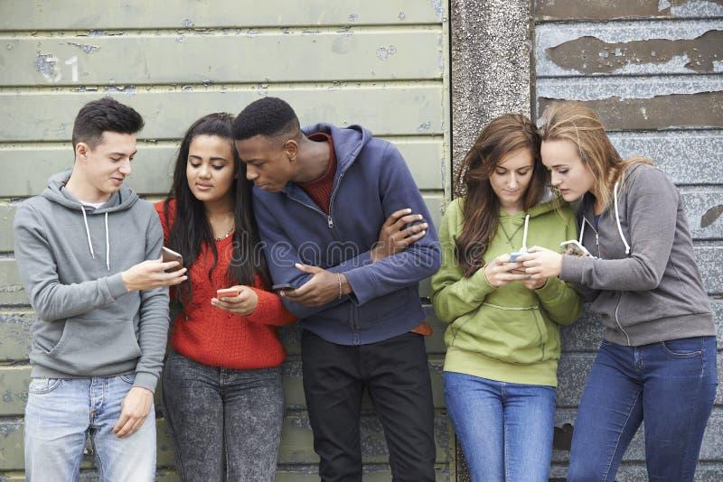 Gruppo di adolescenti che dividono messaggio di testo sui telefoni cellulari immagini stock