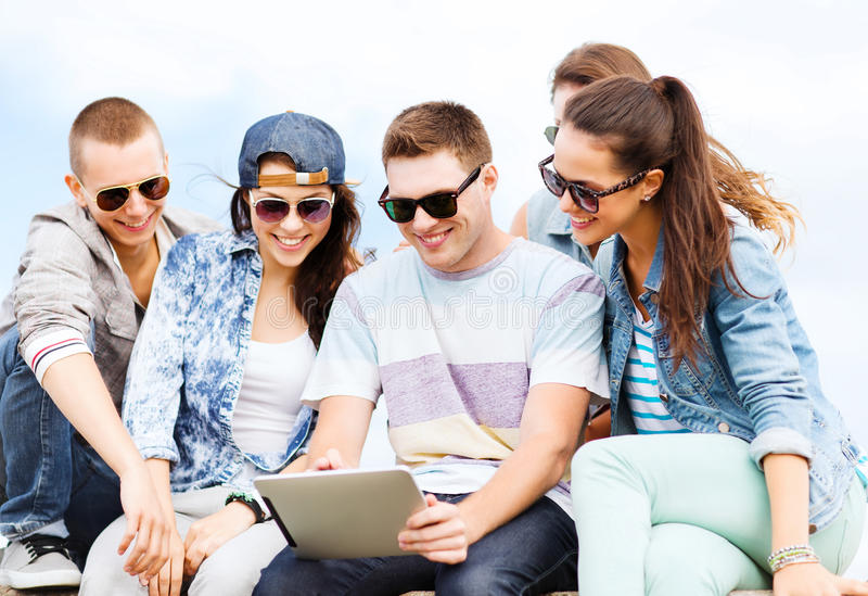 Gruppo di adolescenti che esaminano il pc della compressa fotografia stock