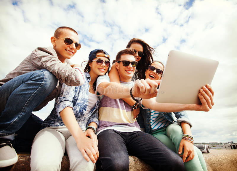Gruppo di adolescenti che esaminano il pc della compressa immagini stock libere da diritti