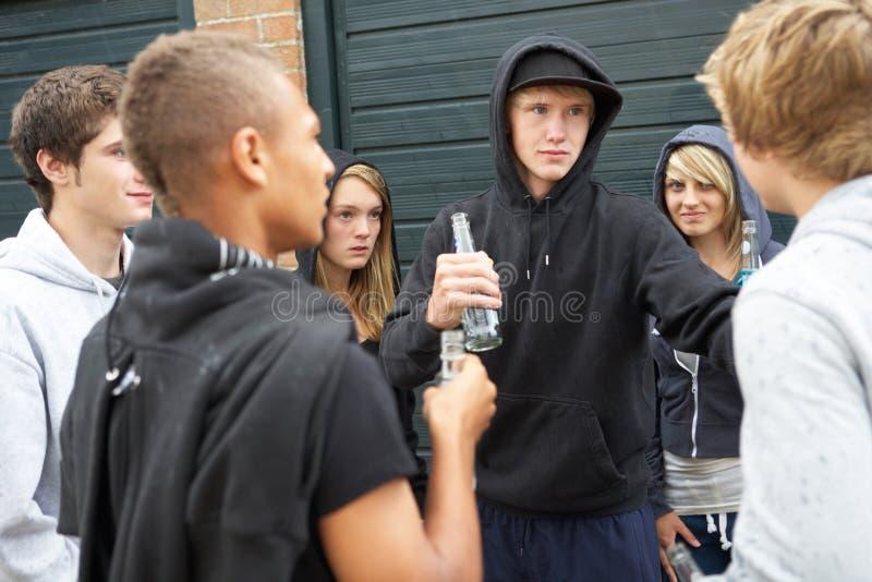 Gruppo di adolescenti minacciosi che appendono fuori fotografie stock