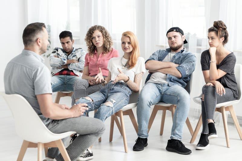 Gruppo di adolescenti ribelli che parlano con psicoterapeuta circa fotografia stock