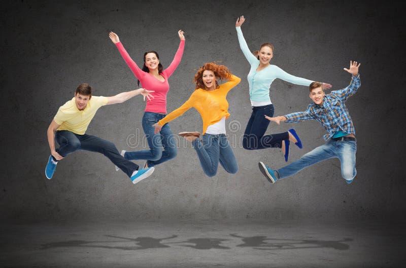 Gruppo di adolescenti sorridenti che saltano in aria fotografie stock libere da diritti
