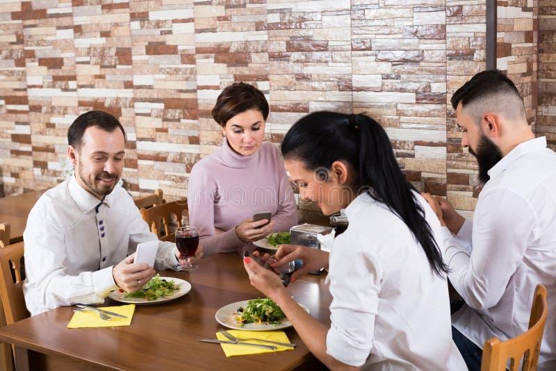 Gruppo di adulti cenando con gli smartphones immagine stock libera da diritti