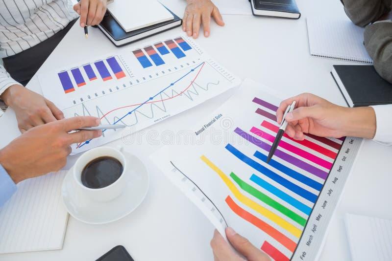 Gruppo di affari che analizza i grafici dell'istogramma immagini stock libere da diritti