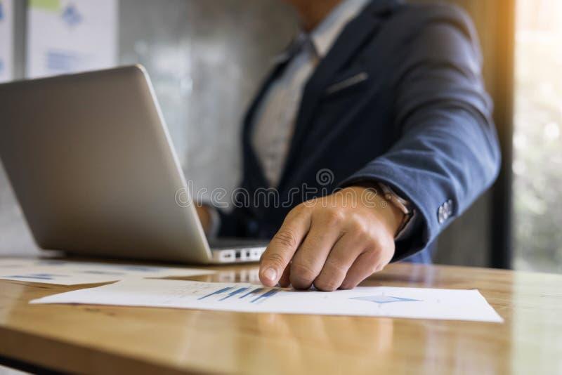 Gruppo di affari che analizza il docume dei grafici di reddito e dei grafici di strategia fotografia stock