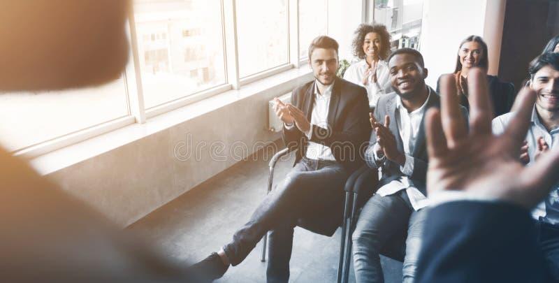 Gruppo di affari che ascolta l'altoparlante alla riunione fotografie stock
