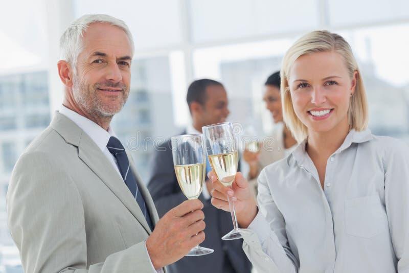 Gruppo di affari che celebra con il champagne e che esamina macchina fotografica immagine stock libera da diritti