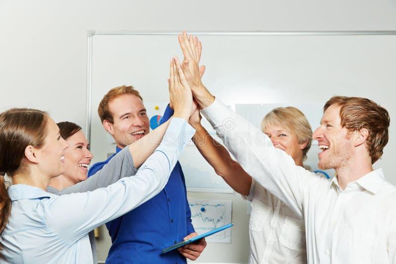 Gruppo di affari che dà livello cinque nell'ufficio immagini stock