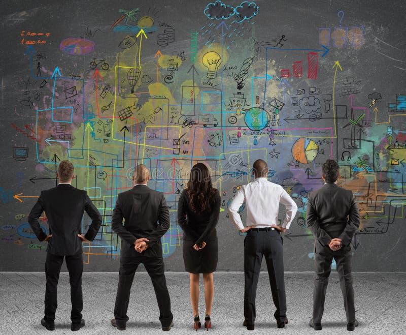 Gruppo di affari che disegna un nuovo progetto immagine stock
