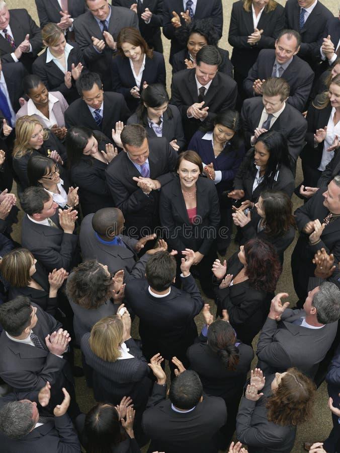 Gruppo di affari che esamina donna nel mezzo fotografia stock