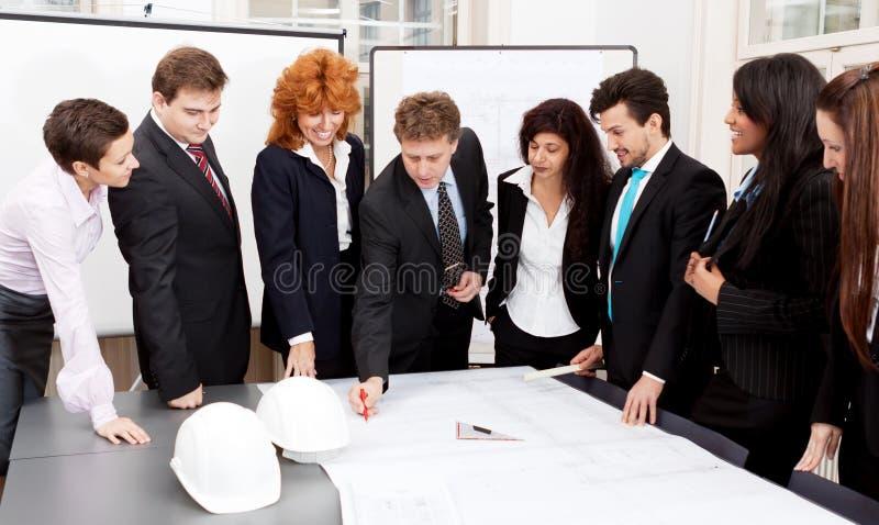 Gruppo di affari che guarda progetto di architettura fotografie stock