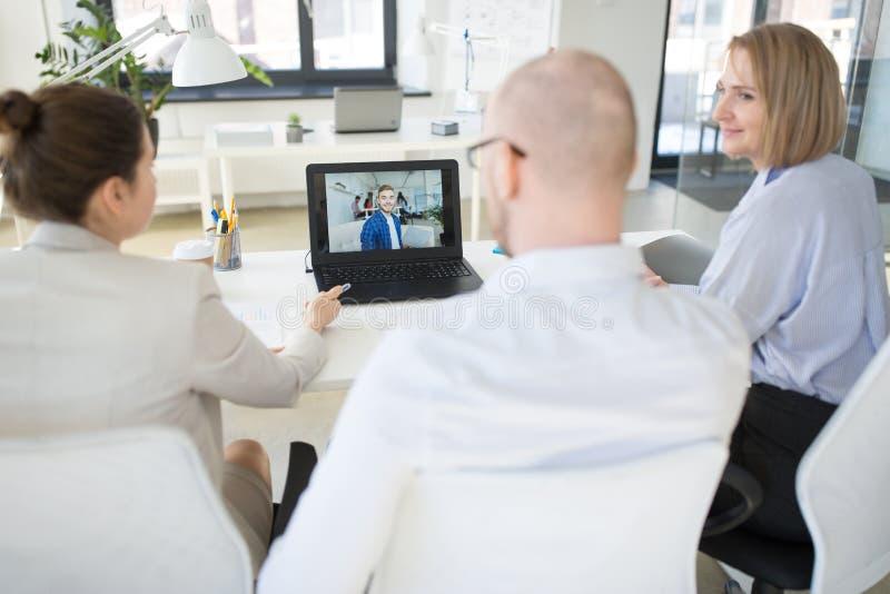 Gruppo di affari che ha videoconferenza all'ufficio immagini stock