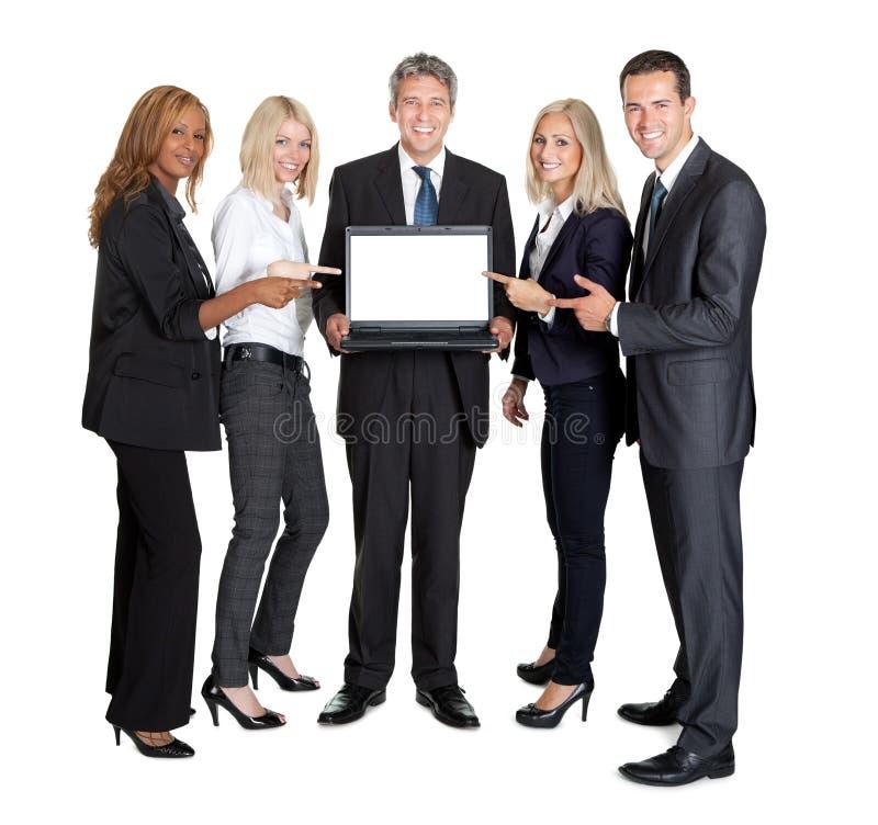 Gruppo di affari che indica al computer portatile fotografia stock