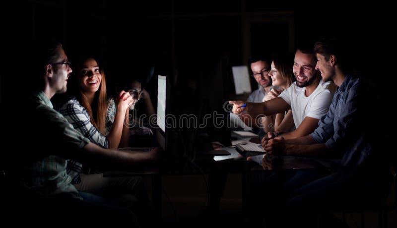 Gruppo di affari che lavora fuori orario con il computer alla notte ed alla scarsa visibilità fotografie stock