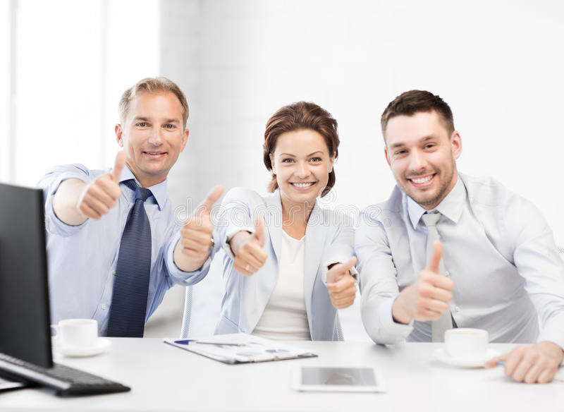 gruppo di affari che mostra i pollici su nell'ufficio fotografia stock