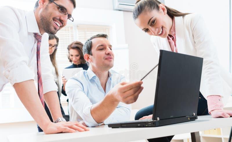 Gruppo di affari che riferisce al capo che ha riunione in ufficio immagini stock