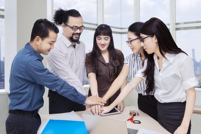 Gruppo di affari che si prende per mano nella sala del consiglio fotografie stock