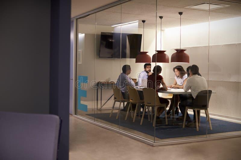 Gruppo di affari corporativi alla tavola in un cubicolo della sala riunioni fotografia stock