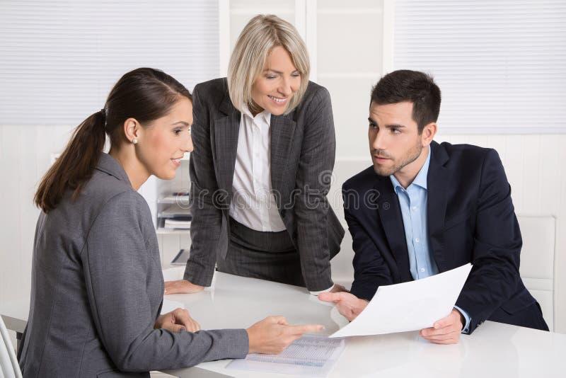 Gruppo di affari dell'uomo e della donna che si siedono intorno ad una tavola che parla con fotografie stock libere da diritti