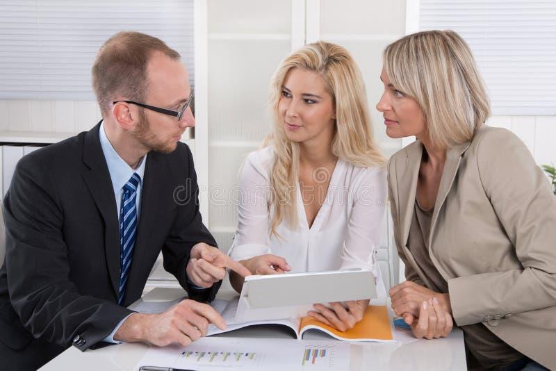Gruppo di affari dell'uomo e della donna che si siedono intorno allo scrittorio in una riunione fotografia stock