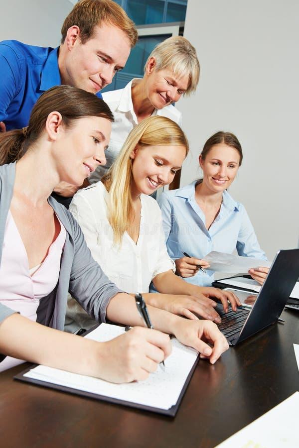 Gruppo di affari facendo uso di collegamento a Internet con il computer portatile fotografia stock