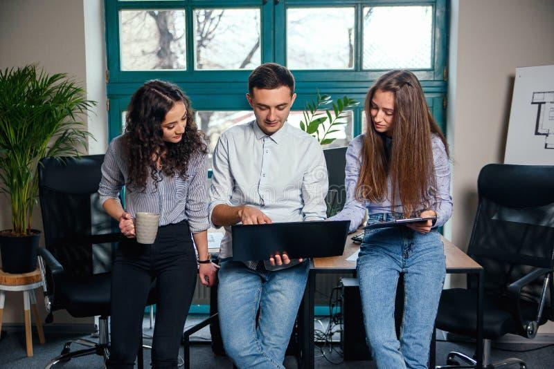 Gruppo di affari di giovani architetti o progettisti che creano nuovo progetto mentre lavorando nell'ufficio alla moda moderno co fotografie stock libere da diritti
